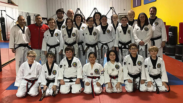Visiting master poses with master and a large group of black belt students.