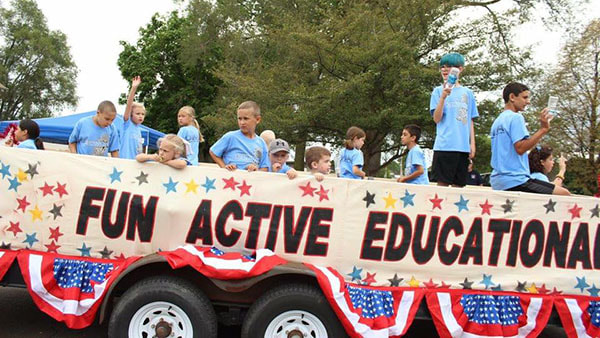 Several students sit on the DIMA float during the annual Riverfest parade.