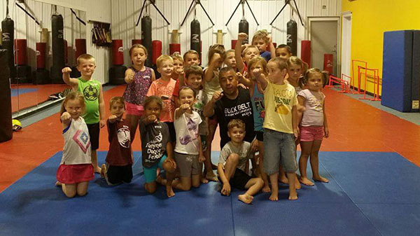 Martial arts master kneels with young self defense students who pose with fists in the air.