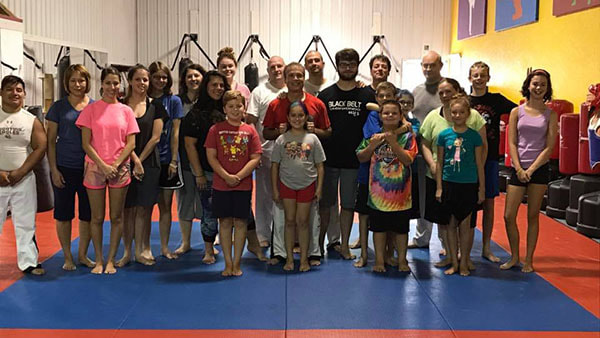 Martial arts master and large group of self defense students pose.