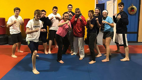 Martial arts master and self defense students pose in fighting stance.