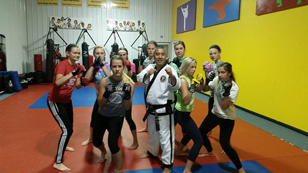 Taekwondo master and female self defense students pose in fighting stance.