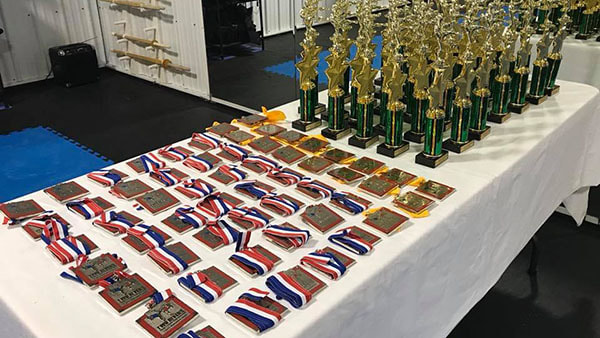 Several trophies and medals laid out on a table in preparation for a tournament.